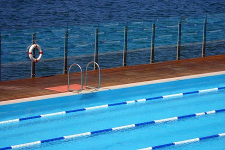 Swimming pool by the sea with a life-buoy and ladder Banque d'images