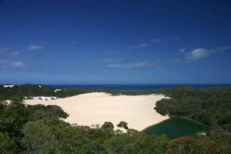 Dune in the middle of the rain forest, with a small green lake (Fraser Island, Australia)