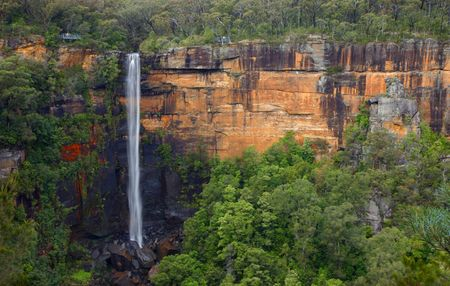 Water fall on a red cliff with vegetation (Australia) Stock Photo
