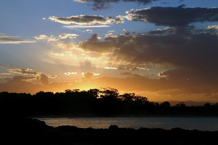 Dramatic sunset on the silhouette of a tropical forest (Australia) photo