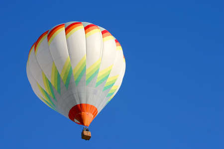 Hot air balloon in flight isolated on blue sky Stock Photo