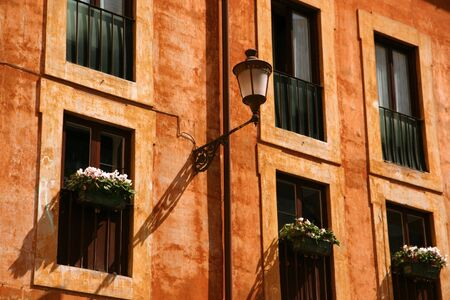 Classic facade with windows, flowers and a lamp photo
