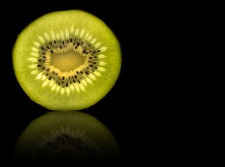 Kiwi slice isolated on black with reflection