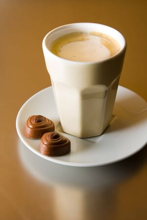 A cup of cappuccino with two coffee chocolates photo