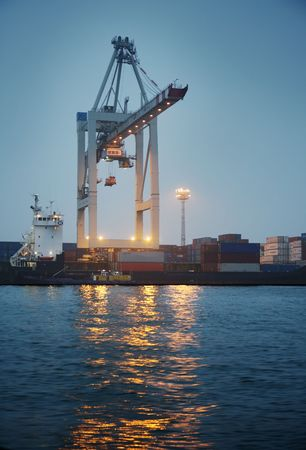 shipload: Crane loading containers in a cargo ship at night.