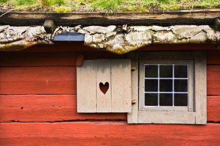 Window of a red wooden cottage photo