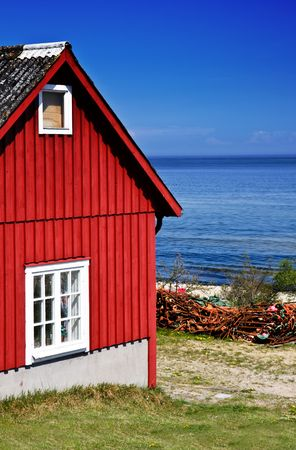 architecture bungalow: Red fishing hut with nets on the coast (Sweden) Stock Photo