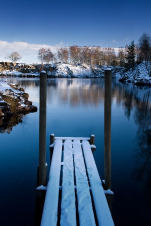 Wooden deck on the shore of a small lake in winter (Sweden). Stock Photo