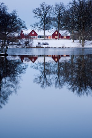 Red home a dawn near a lake with its reflection. photo