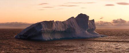 Large iceberg floating in sea at dusk. Horizontally framed shot.