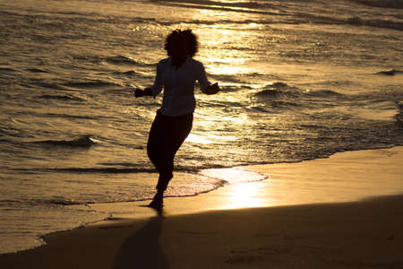 keep fit: A woman runs the evening at the beach. She its doing sport to keep fit