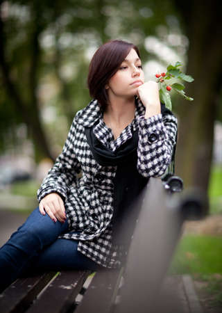 Lonely girl siting on a bench in an autumn park Stock Photo - 10787209