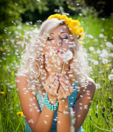Blond girl blowing on white dandelion Stock Photo - 10787204