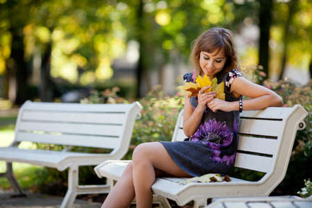 attitude girls: Lonely girl siting on a bench in an autumn park Stock Photo