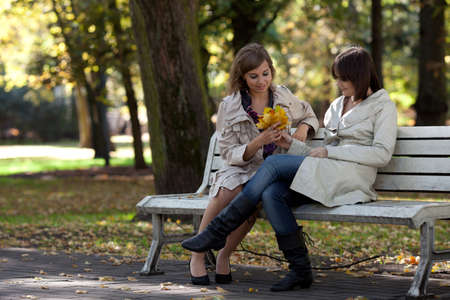 two friends: Two girls students gossiping in autumn park Stock Photo