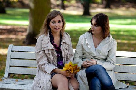 dos personas hablando: Dos chicas estudiantes de chismes en el oto�o de parque Foto de archivo