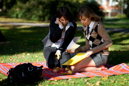 Two girls students sitting in autumn park photo