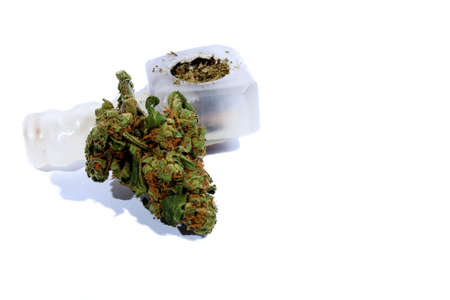 Isolated marijuana bud laying by a pipe   photo
