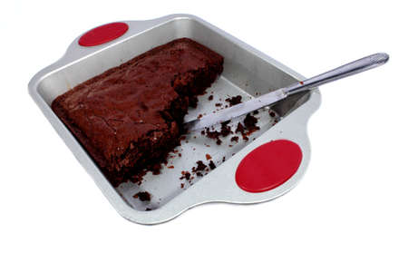 Isolated dessert chocolate brownie filled with chocolate chips with pan and knife  Stock Photo