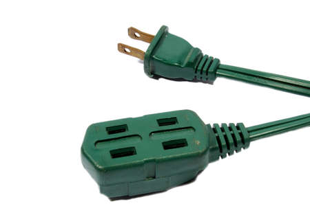 Isolated green plastic extension cord with 3 different outlets