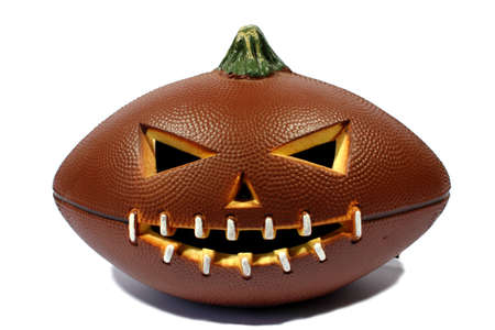 Isolated brown halloween football carved out as a jack o lantern   photo