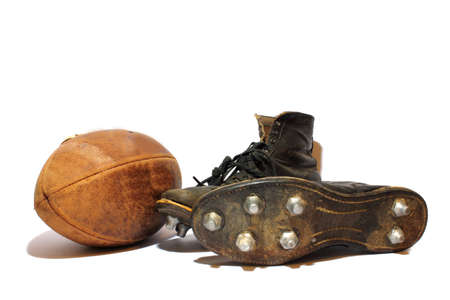 Antique football and cleats sitting on an isolated background