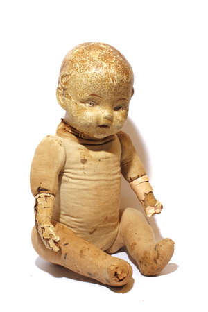 Isolated antique play doll toy starting to fall apart