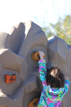 Close up view of a child climbing a rock wall   Stock Photo