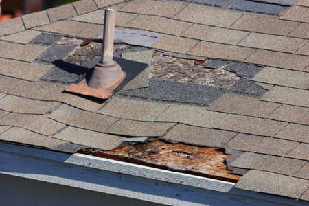 damaged roof: A close up view of shingles being blown off a roof and other roof damage