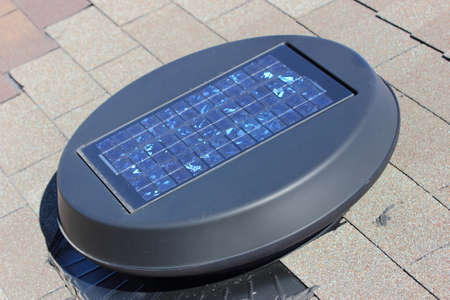 A close up view of a solar attic fan installed on a roof top