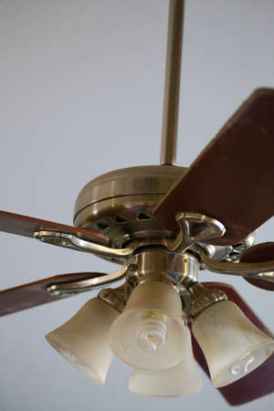 Close up view of a ceiling fan with brown wooden blades and four light bulbs Stock Photo