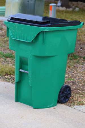 A green and black trash can sitting on the side of the curb 版權商用圖片