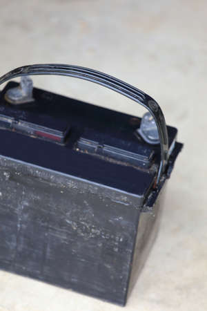 Close up view of a car battery sitting on the ground   photo