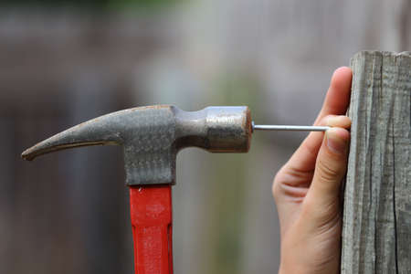 Close up view of a black and red hammer being used to hammer a nail into a fence post