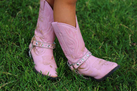 Close up view of a pair of pink cowboy boots in the grass