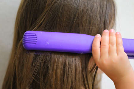 Close up view of a young girl straightening her hair  Stock Photo