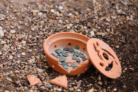 minted: Close up view of ancient roman coins laying in a broken terra cotta vase