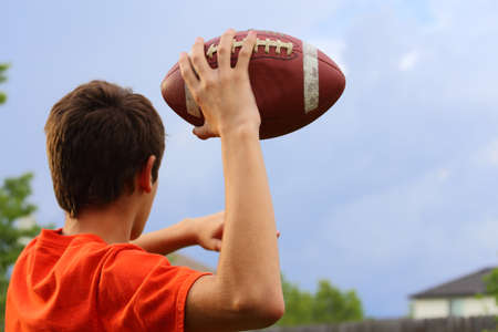 A young man cocking his arm back and getting ready to throw a football
