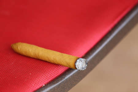 A close up view of a cigar burning laying on a chair photo
