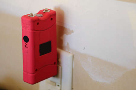A close up view of a pink taser being plugged in to charge photo