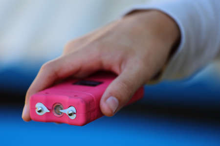Close up view of someone holding a pink taser photo
