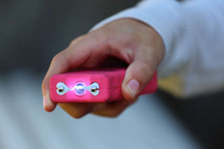 Close up view of someone holding a pink taser