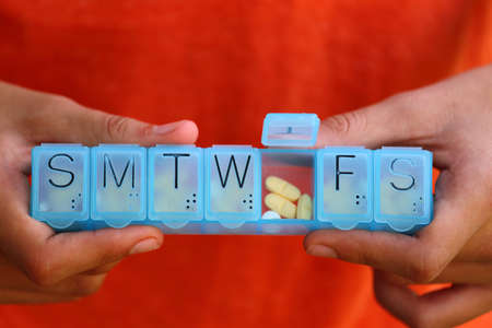 Close up view of someone holding a blue plastic 7 day pill box filled with pills Stock Photo