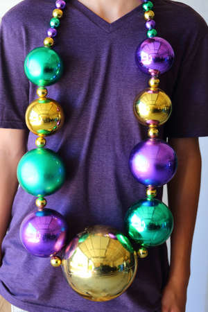 A close up view of someone wearing large mardi gras beads for carnival