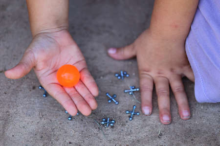 A close up view of someone playing jacks with a orange ball
