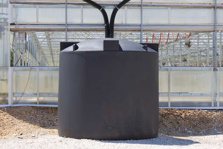 A couple of rain water collection tanks used to catch rain water off of a greenhouse. photo