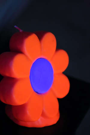 A close up view of a red and blue flower candle under a black light