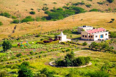 Distant farm house  school  hospital with temple Stock Photo