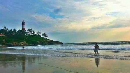 kovalam: Two couples enjoying at Kovalam beach near light house, Thiruvanathapuram, Kerala, India