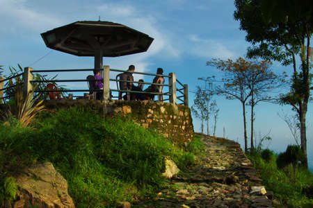 People sitting at a mountain top view point gazebo, at Jhandi, North Bengal during Sunset 스톡 콘텐츠